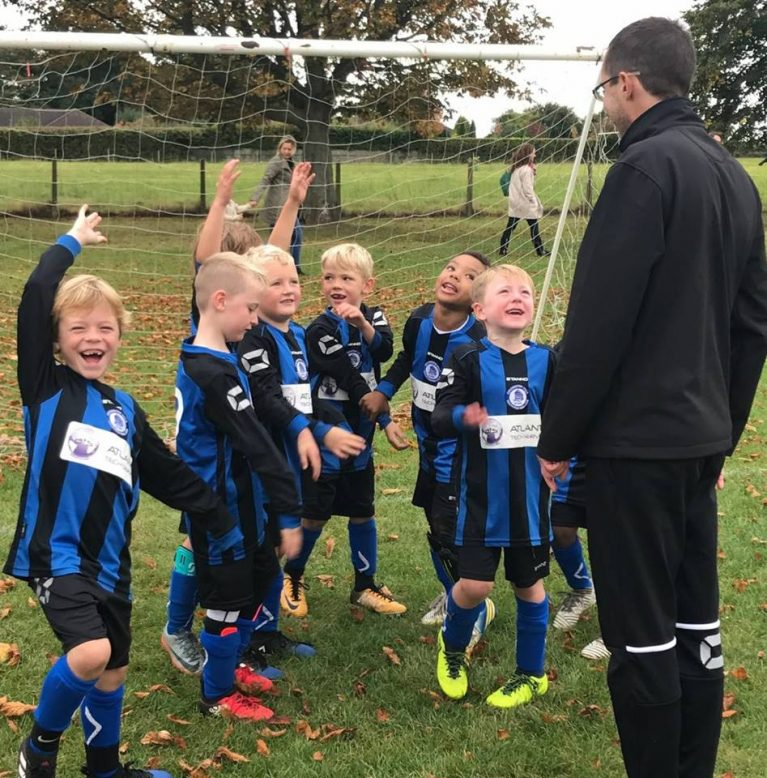 Young footballers having fun and lots of smiles with their coach at Colchester Villa